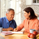 17068-a-woman-and-older-man-sitting-at-a-table-pv