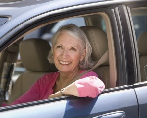 Smiling elderly woman in driver's side of the car